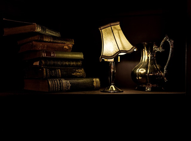 pile of books, with a dim lamp on the side